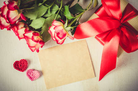 Empty greeting card with copy space for your own text. Red roses and gift box for birthday Valentines or Mothers day. Stock Photo