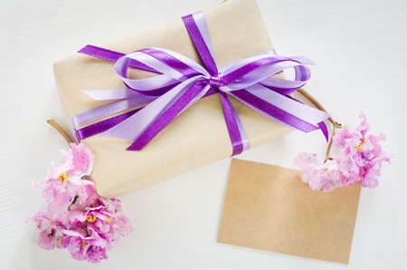 Present or gift box and empty greeting card with delicate flowers from above. Holiday concept. Flat lay style, top view.