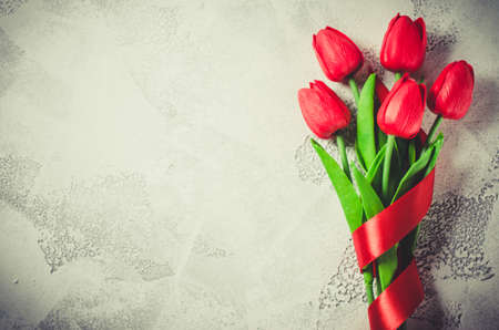 Bouquet of red tulips with ribbon on white background. Spring flowers. Spring background. Greeting card for Valentine's Day, Woman's Day and Mother's Day. Top view, copy space. Stock Photo
