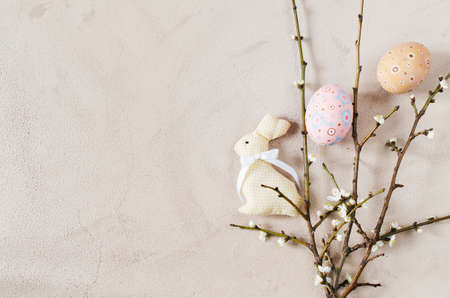 Easter background in beige color with spring flowering branches and easter eggs. Top view, copy space.