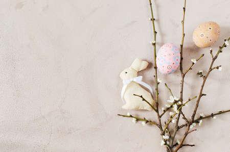 Ostern-Hintergrund in der beige Farbe mit blühenden Niederlassungen und Ostereiern des Frühlinges. Draufsicht, Kopie, Raum.