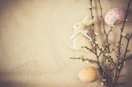 Easter background in vintage style with spring flowering branches and easter eggs. Top view, copy space.
