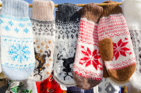 Mittens At Winter Christmas Market. A variety colorful knitted of woolen mittens hanging on a rope. Christmas gift or souvenir. Foto de archivo