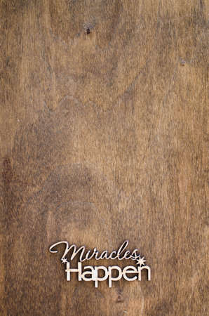 Inscription miracles happen on a wooden background. Concept of inspiration and hope. Copy space for your text, top view.