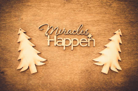 Inscription miracles happen on a wooden background. Concept of inspiration and hope. Top view. Stock Photo