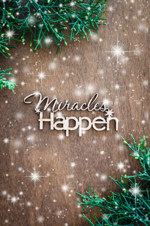Inscription miracles happen and fir branches on a wooden background. Concept of inspiration and hope. Top view. Snow effect. Standard-Bild