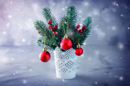 Christmas background with xmas fir branches and decorations in the snow atmosphere. Christmas greeting postcard. Toned, snow effect. Stock Photo
