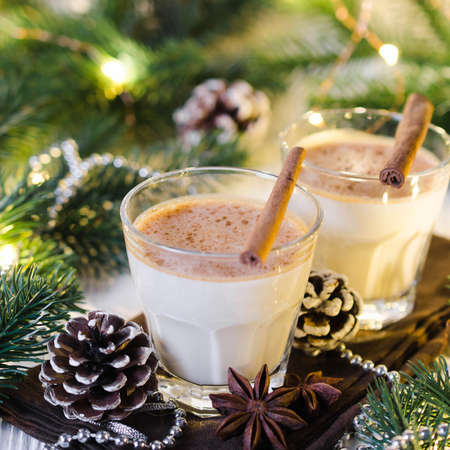 Christmas Traditional Homemade Eggnog in Festive Atmosphere. Fir branches with Christmas Lights and Decorations. Milk Cocktail with Spice. Selective Focus. Copy Space.
