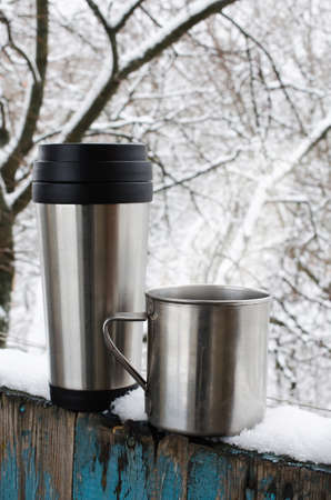 Iron mugs of hot drink on a snow covered terrace.