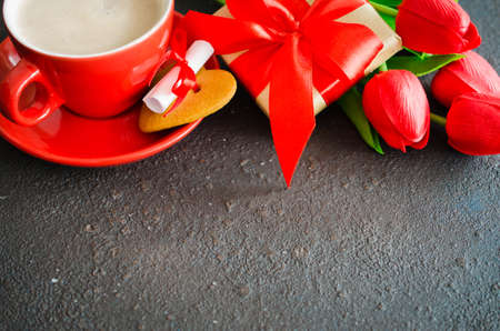 Romantic composition for Valentines Day, Birthday or Mothers Day. Red coffee cup, cookie in the shape of a heart with a note, gift box and red tulips.