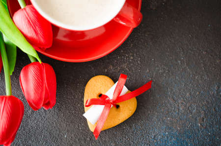 Romantic composition for Valentines Day, Birthday or Mothers Day. Red coffee cup, cookie in the shape of a heart with a note and red tulips. 写真素材