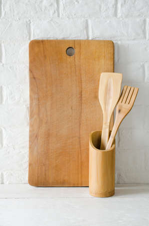 Simple rustic kitchenware: wooden or bamboo cutlery and cutting board in interior of white kitchen. Rustic style. Home Kitchen Decor.