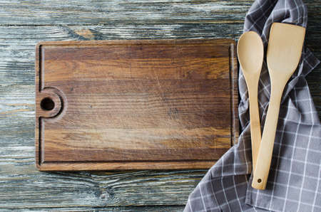 Culinary background with rustic kitchenware: wooden or bamboo cutlery, vintage cutting board and towel against vintage wooden background. Rustic style. Home Kitchen Decor. View from above.