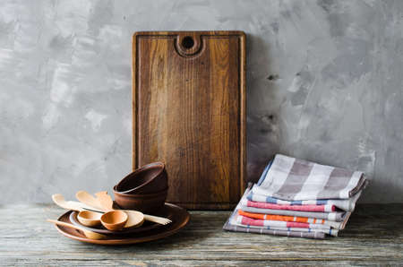 Simple rustic kitchenware: ceramic plates, wooden or bamboo cutlery, vintage cutting board and towels in interior of kitchen. Rustic style. Home Kitchen Decor. Stock Photo