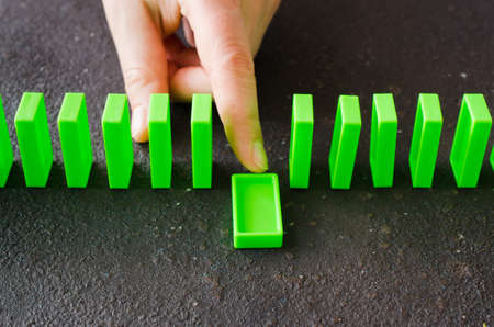 Domino effect - row of green dominoes on dark background. Hand pushing domino piece. The concept of a weak link.