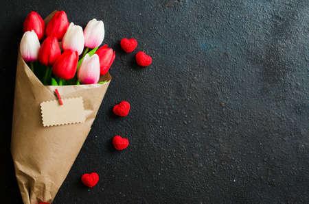 Fondo de vacaciones con flores de primavera. Ramo de tulipanes y corazones decorativos sobre fondo oscuro. Tarjeta de felicitación para San Valentín, día de la mujer o de la madre. Endecha plana, vista superior, espacio de copia Foto de archivo