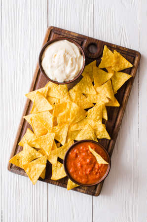 Nachos corn chips with spicy tomato and cheese sauces. Stok Fotoğraf