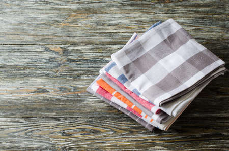 Stack of kitchen towels or napkins over the rustic wooden table. Archivio Fotografico