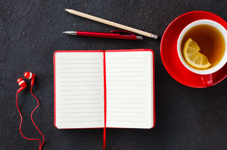 Blank red notebook with pen, headphones and cup of tea on dark table. Business still life, office or education concept. Top view of working desk.