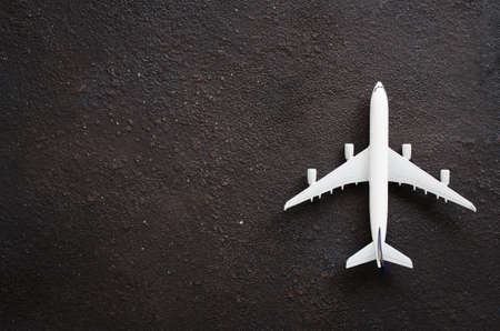 Miniature airplane on a dark background. Travel concept. Flat lay with copy space.