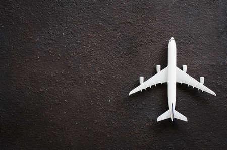 Miniatuur vliegtuig op een donkere achtergrond. Reisconcept. Plat leggen met kopieerruimte. Stockfoto