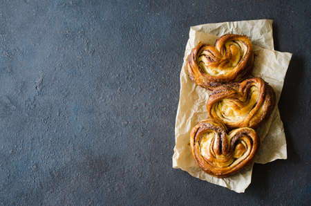 Baked fresh fragrant cinnamon buns. Traditional homemade pastries on dark background. Rustic style. Фото со стока