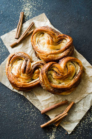 Baked fresh fragrant cinnamon buns. Traditional homemade pastries on dark background. Rustic style. Stock fotó