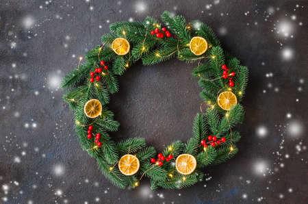 Weihnachtstürkranz aus Tannenzweigen mit Weihnachtsbeleuchtung und Dekorationen auf dunklem Hintergrund. Kopieren Sie Platz im mittleren Rahmen und leeren Sie das Mock-up für Text.