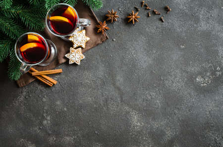Christmas mulled red wine with spices and fruits on a dark background. Traditional hot drink at Christmas time. Holiday atmosphere on dark background.