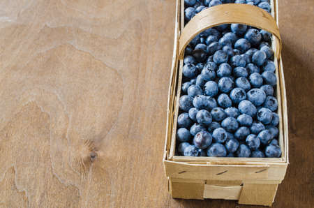 Fresh organic blueberries in a basket on wooden background. Copy space. Top view or flat lay