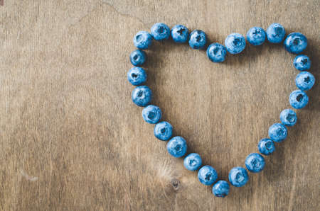 Fresh organic blueberries in form of heart on wooden background. Heart health concept. Disease prevention