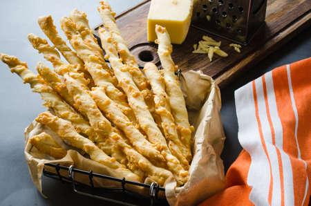 Käsestück. Grissini mit Käse auf dunklem Hintergrund, Konzept für Snacks oder Partyzeit Standard-Bild
