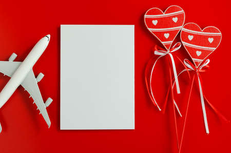 Travel planning on Valentines day . Travel concept, mockup. Blank white paper, wooden hearts and model of passenger plane on red background. Top view or flat lay. Copy Space.
