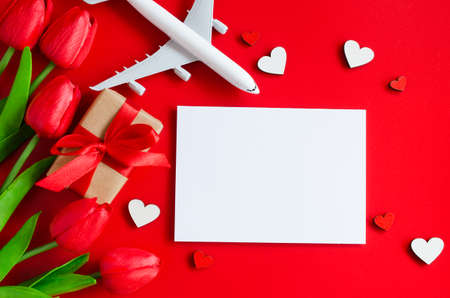 Travel planning on Valentines day . Travel concept, mockup. Blank white paper, red tulips, gift box and model of passenger plane on red background. Top view or flat lay. Copy Space.