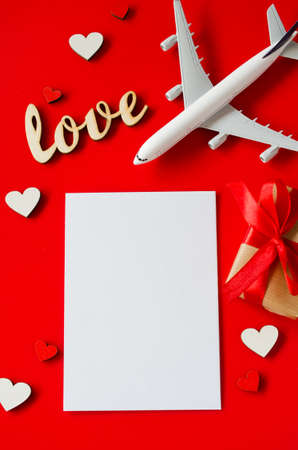 Travel planning on Valentines day . Travel concept, mockup. Blank white paper, model of passenger plane, gift box and inscription love on red background. Top view or flat lay. Copy Space.