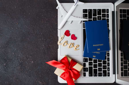 Travel planning on Valentines day. Travel concept. Airplane model, laptop, passports and gift box on dark background. Top view or flat lay. Copy Space.