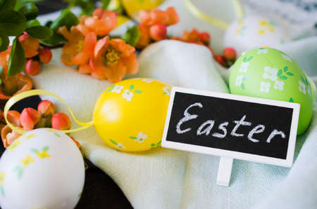 Easter background with decorative eggs, blossoming spring branch and inscription Easter on a chalk nameplate. Standard-Bild