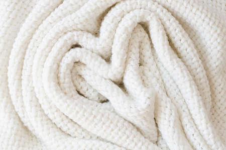 Beige knitted woolen background. Knitwear fabric texture.