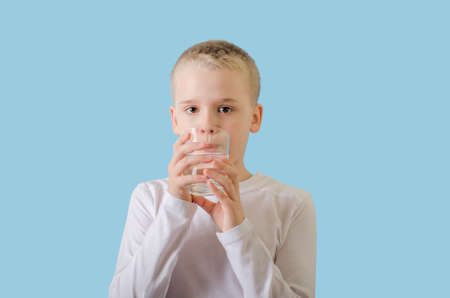 Cute child drinking clean water from glass. Blond little boy with water glass, looking at the camera.