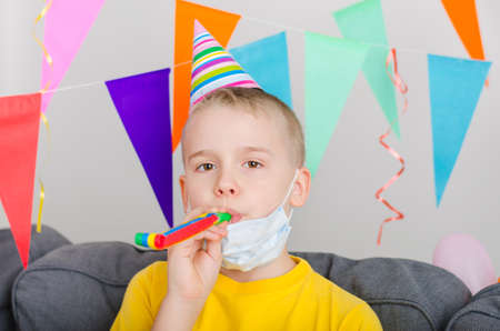 Happy boy took off his face mask and blowing in festive pipe. Child celebrates quarantined birthday. Festive event in isolation. Social distance. Stock fotó