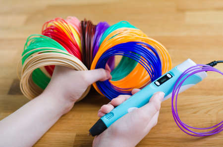 Child's hands hold kit colored ABS plastic in coils and 3d pen. Handmade. STEM education. New technology. Hobby after school.