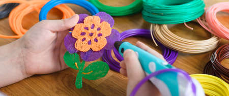 Child using 3D pen. Children hands making flower from colored ABS plastic. Creative hobby at home, technology, leisure, education concept. Selective focus.