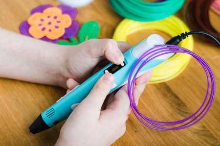 Child using 3D pen with colored ABS plastic. Creative hobby at home, technology, leisure, education concept. Selective focus.
