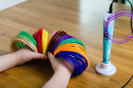 Child's hands hold kit colored ABS plastic in coils for 3d pen and printer. Handmade. STEM education. New technology. Hobby after school. Фото со стока