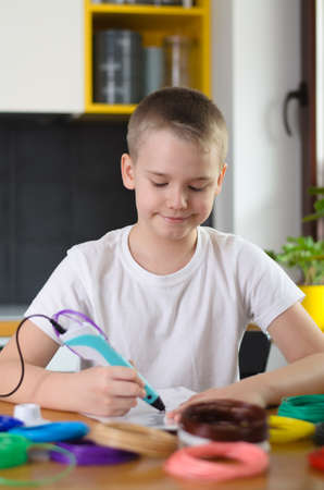 Child using 3D pen. Boy draws on stencil by colored ABS plastic at home. Creative hobby at home, technology, leisure, education concept. Selective focus.