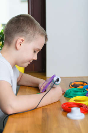Child using 3D pen. Happy boy making flower from colored ABS plastic. Creative hobby at home, technology, leisure, education concept. Фото со стока