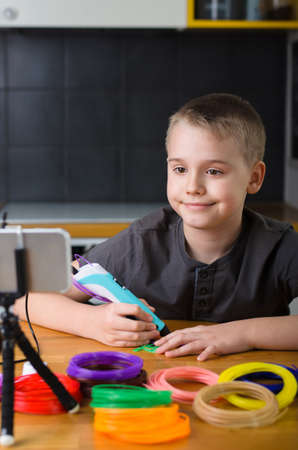 Child creating with 3d printing pen. Happy boy does something with colored ABS plastic and using online lesson. Creative hobby at home, technology, leisure, education concept. Фото со стока