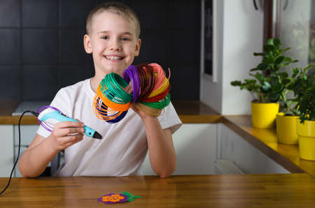 Happy boy holds kit colored 3D pen and ABS plastic. Child using 3D pen. Creative hobby at home, technology, leisure, education concept. Selective focus.