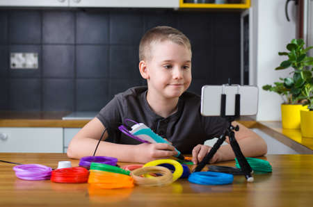 Child creating with 3d printing pen. Happy boy does something with colored ABS plastic and using online lesson. Creative hobby at home, technology, leisure, education concept. Stock fotó