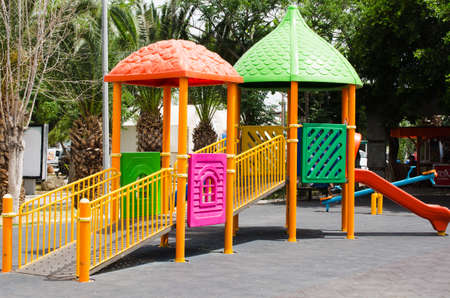 Colorful children playground activities in public park surrounded by green trees.